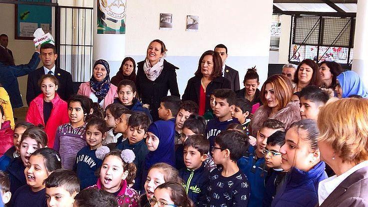 Ein Haufen Kinder, dahinter Lehrpersonal bestaunen den deutschen Bundespräsidenten