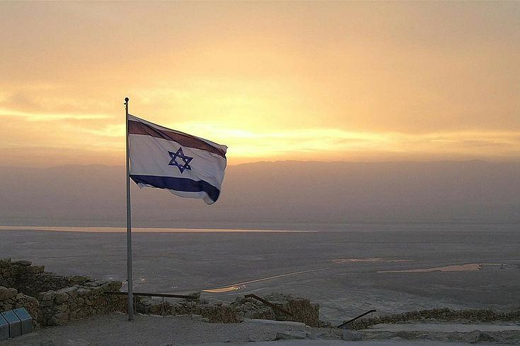 Israelische Flagge mit dem Davidsstern weht über einer weiten Ebene im Abend/Morgenlicht