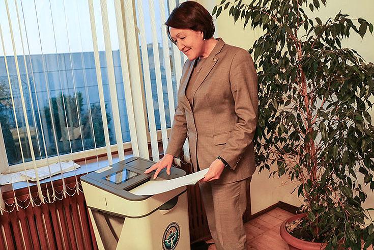 Nurzhan Shaildabekova zeigt wie eine elektronische Wahlurne funktioniert