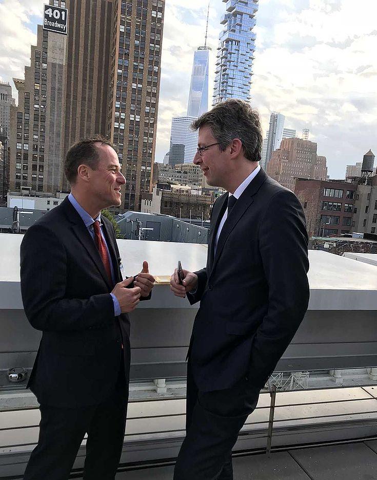 Zwei Männer auf einem Balkon vor der New-Yorker Skyline in angeregter Unterhaltung.