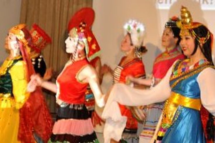 Auf einer Bühne drehen sicdh Tänzerinnen in bunten Kostümen