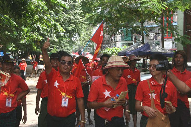 Wahlkampfparade in den Straßen Yangons mit Menschen in roten Shirts
