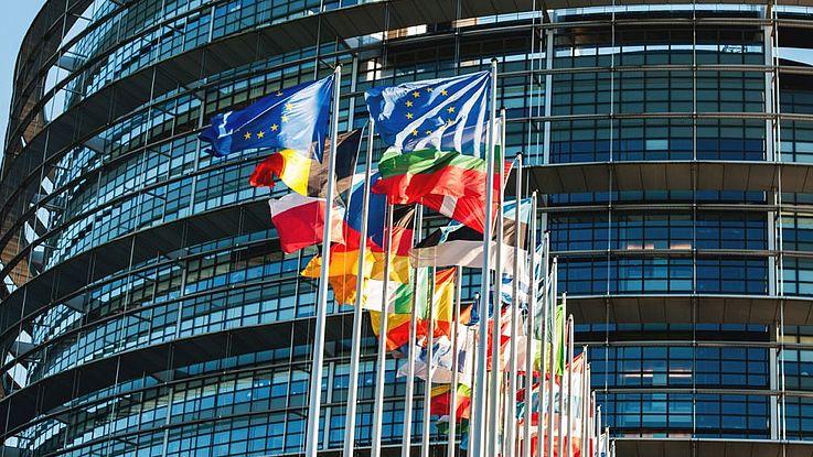 Die Flaggen der EU-Staaten vor dem Kommissionsgebäude in Brüssel in starkem Wind flatternd.