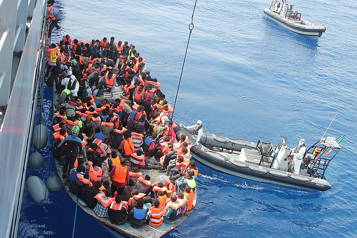 Ein übervolles Schlauchboot liegt schwankend an der haushohen Bordwand eines Rettungsbootes, das gerade versucht, die Menschen zu bergen.
