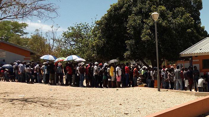 Vor einem flachen Gebäude in Namibia steht eine lange Schlange von wartenden Menschen, die zur Wahl gehen