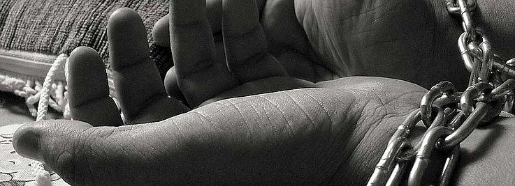 Die beiden Hände einer Frau in Ketten gefesselt