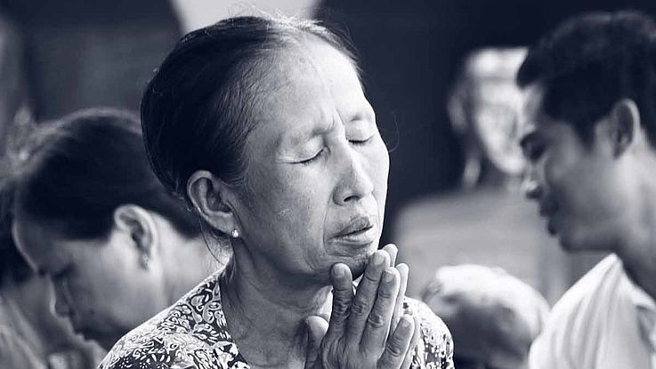 EIne ältere Frau sitz mit zum beten gefaltenen Händen auf dem Boden. Ihre Augen sind geschlossen. Ihr Ausdruck ist traurig bis hoffnungsvoll.