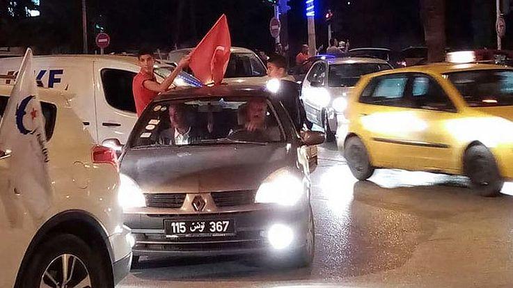 Es ist abends auf einer Straße in Tunis. Mehrere Autos, Fahrer schwenken die Flagge von Tunesien