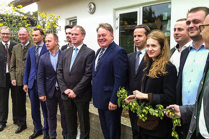 Die Besucher aus Rumänien stehen mit Staatsminister Brunner vor dem sogenannten Hopfenhaus in Steinbach