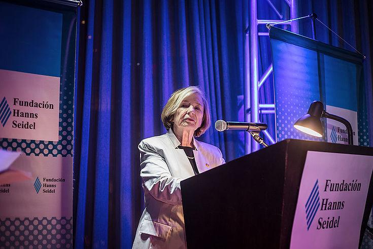Ursula Männle steht hinter einem Rednerpult auf der Bühne. HSS-Roll-ups stehen im Hintergrund.