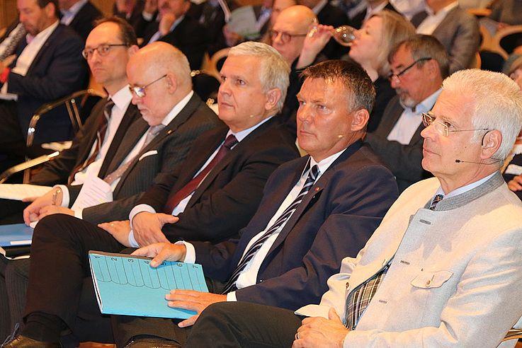 Erste Reihe des Plenums. Fünf Herren sitzen mit Unterlagen auf dem Schoss und lauschen.