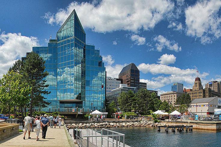 Halifax. Wasser zur Rechten (wahrscheinlich ein künstlicher Teich), dort auch hoher Flaggenmast mit der Kanada-Flagge. Links ein verglaster Bürobau.