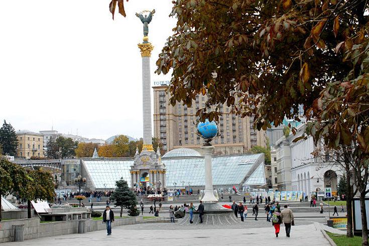 Teilansicht des Kiewer Maidan am Wahltag mit einem Baum im Vordergrund, einer Säule sowie Gebäuden im Hintergrund und einigen Menschen