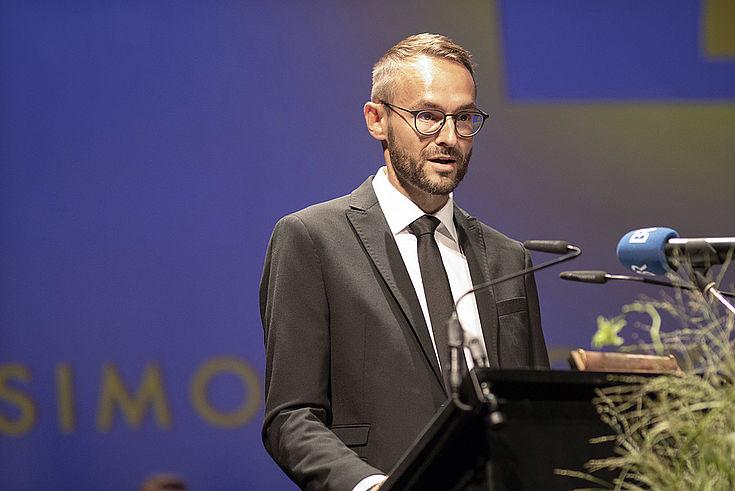 Mann in sehr gut sitzendem Anzug, förmlicher schwarzer Krawatte und runder Brille am Rednerpult