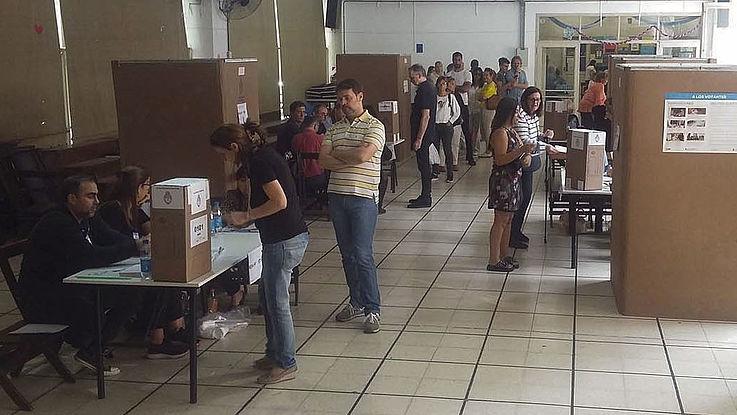 Ein Wahllokal mit einigen Personen in Buenos Aires. Zu sehen sind Wahlkabinen und ein Tisch zur Registrierung