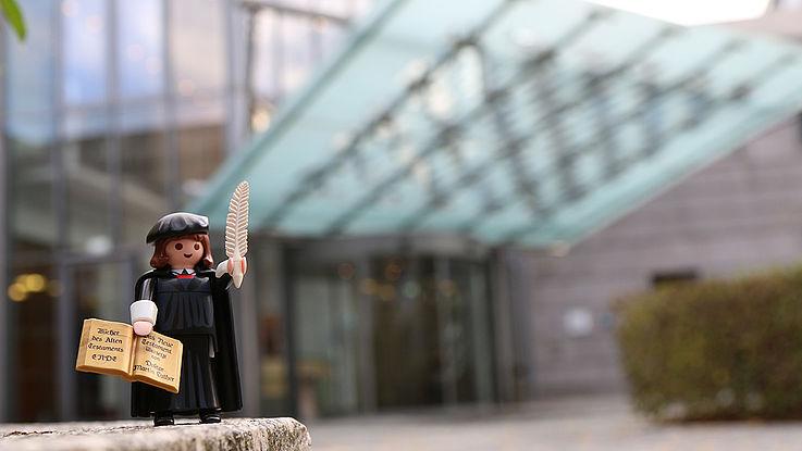 """Eine lustige Legofigur von Martin Luther mit Feder in der linken und Thesen in der rechten Hand steht perspektivisch vergrößert auf einem """"Fels"""" vor der HSS Zentral in München.e"""