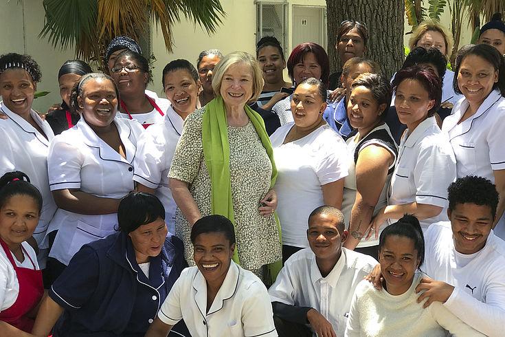 Prof. Ursula Männle inmitten einer Gruppe von Frauen und Männern. Bei der Einweihung einer Küche im Bergzicht Trainingszentrum in Stellenbosch/Südafrika, die von der HSS gesponsert wurde.