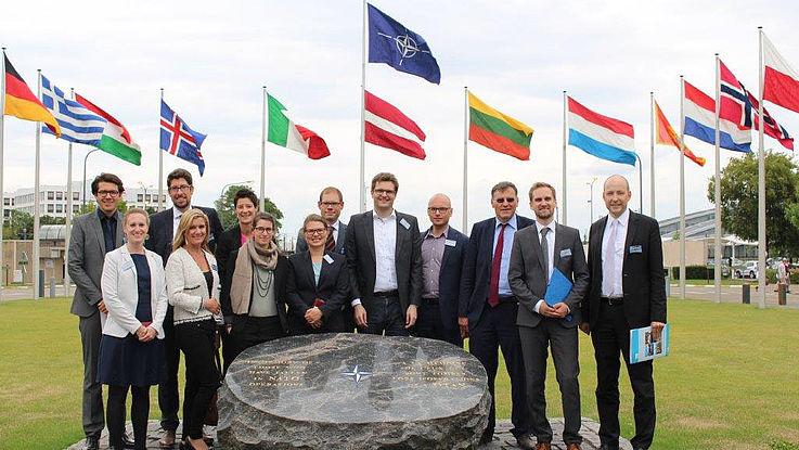 Menschengruppe vor den Fahnen der NATO-Mitgliedstaaten.