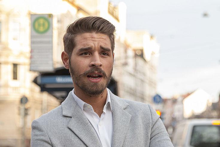 Der Interviewte, ein junger Mann, spricht mit nachdenklichem Gesichtsausdruck. Im Hintergrund ist eine Straße und eine Haltestelle zu sehen.