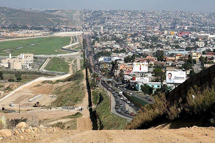 Linke Bildhälfte: grüne Rasenflächen auf US-Gebiet. Vlt ein Golfplatz? Rechte Bildhälfte: dicht gedrängte, wuselig, unordentlich angeordnete Gebäude auf mexikanischer Seite. In der Mitte der Grenzzaun.