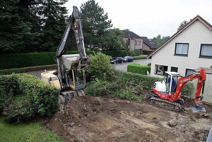 Baustelle in einem brachliegenden Grundstück in einem Wohngebiet. Zwei Bagger bei der Arbeit.