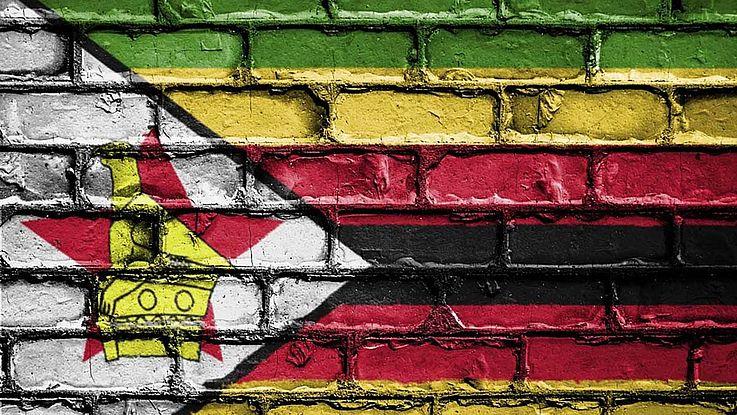 Flagge Simbabwes. Horizontal dreigeteilt mit, auf der linken Seite, einem Dreieck, das spitz in die Flagge ragt, mit Stern und Wappentier.