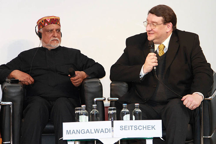 Seitschek, ein untersetzter Mann mit runder Brille spricht mit freundlichem Gesicht ins Mikorfon. Neben ihm sitzt Dr. Vishal Mangalwadi mit orientalisch anmutender Kopfbedeckung.