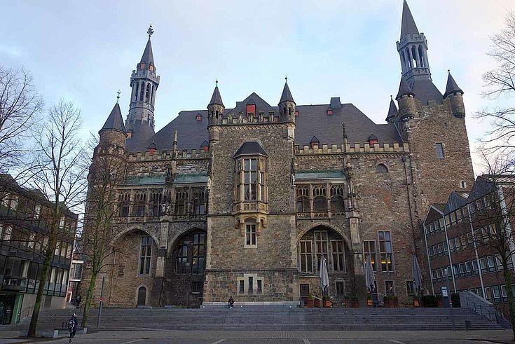 Altes Rathaus aus Ziegeln mit zwei filigranen, spitzen Türmen und runden Tür- und Tor- und Fensterbögen.