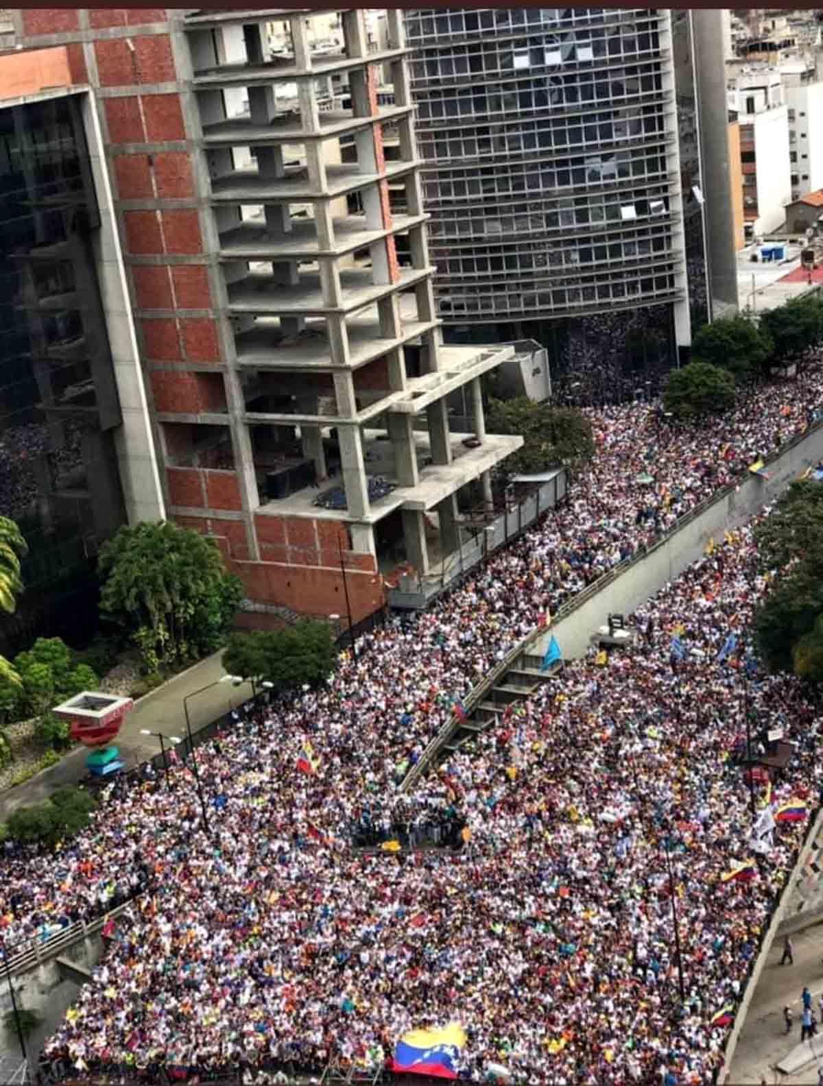 Gewaltige Menschenmenge, tausende, zehntausende, füllt eine breite Straße in Caracas.