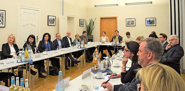 Diskussion an einem langen Konferenztisch mit ca. 15 Personen