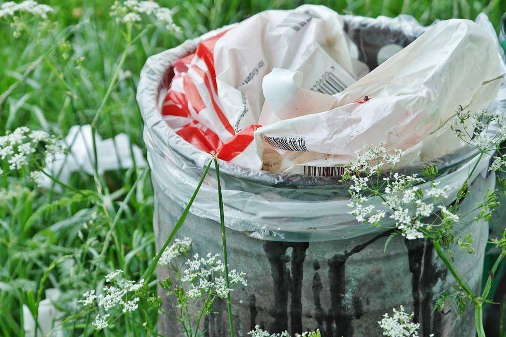 Eine Mülltonne voller Plastiktüten auf einer Wiese