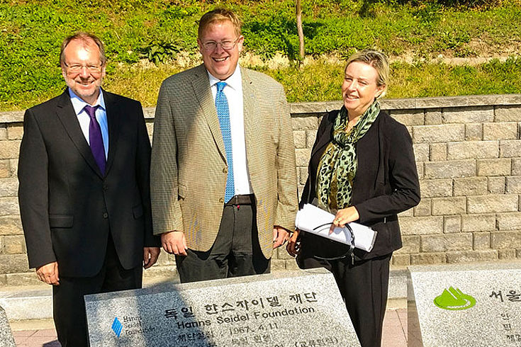 Peter Witterauf, Bernd Seliger und Susanne Luther überzeugen sich vom Engagement für die koreanische Umwelt. Sie stehen vor beschrifteten Gedenksteinen.