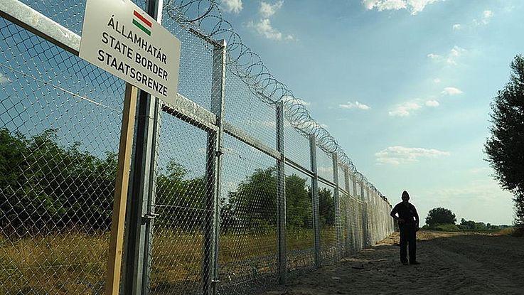 Unfreundlicher Grenzzaun mit unfreundlicher Silhouette eines Grenzpolizisten im Schatten im Hintergrund