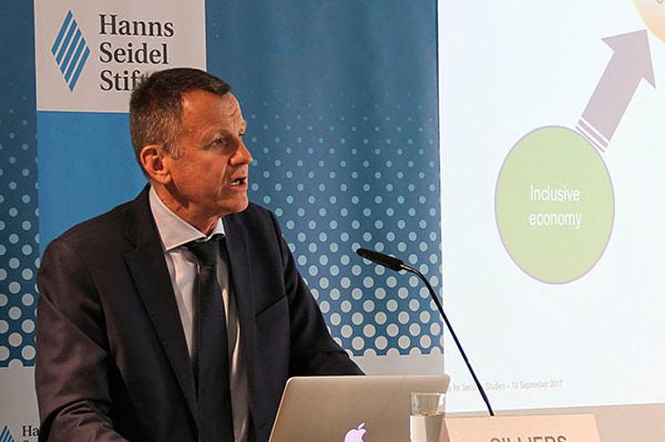 Jakkie Cilliers steht an einem Rednerpult, hinter ihm ein Plakat der Hanns-Seidel-Stiftung