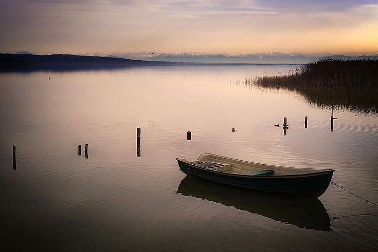Ein Ruderboot liegt vertäut im Abendlicht im ruhigen Wasser des Ammersees (Westufer). Im Hintergrund die Alpenkette