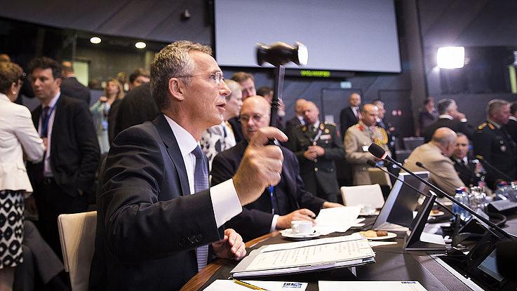 Moderator beim NATO-Treffen in Brüssel. Hämmert gerade mit seinem Hammer auf seinen Tisch, um Ruhe zu bekommen.