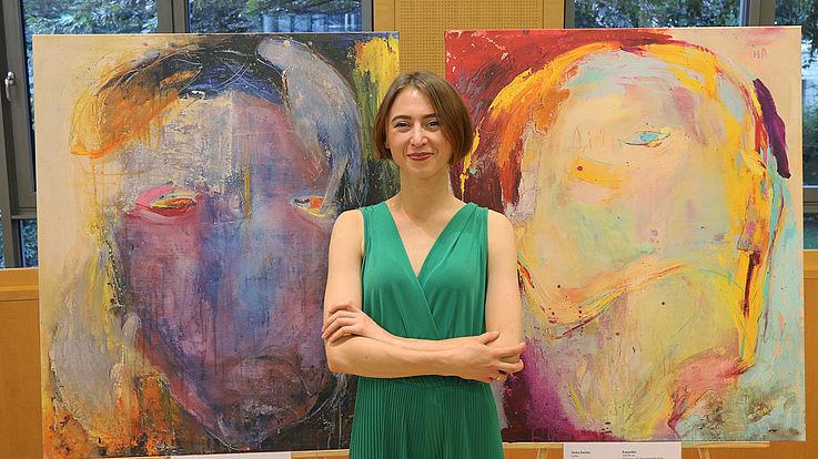 Zirka Savka vor ihren experimentellen Ölgemälden, die Sie der Hanns-Seidel-Stiftung als Schenkung überlässt.