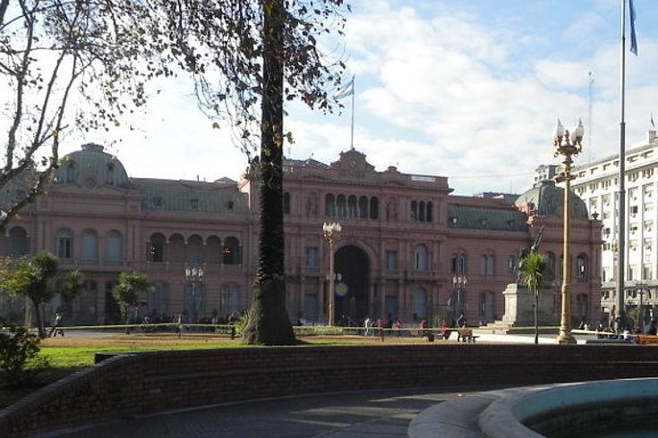 Die Casa Rosada, der argentinische Präsidentenpalast in der Hauptstadt Buenos Aires. Im Vordergrund ist ein Springbrunnen zu sehen. Dahinter ist der rosafarbene Palast.