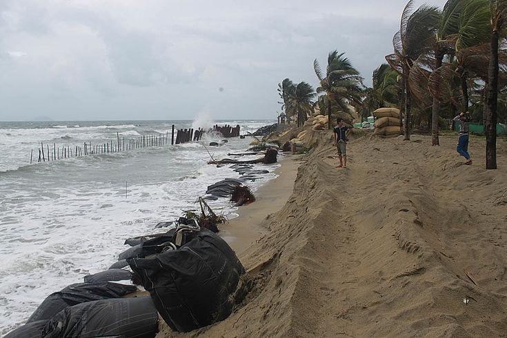 Ein schmaler Sandstrand, befestigt mit Sandsäcken im Sturm. Wellen spühlen den Sand mit sich fort.