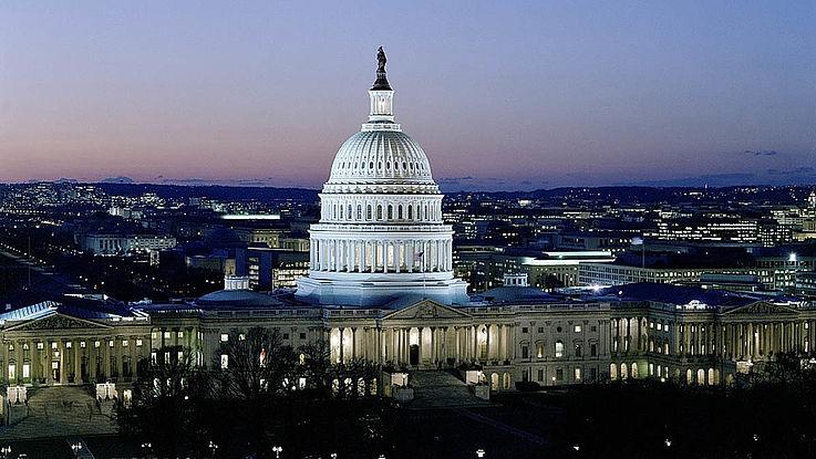 Das Kapitol in Washington aus der Luft fotografiert. Abend- oder Morgenstimmung. Die riesige, weiße Kuppel ragt in den dämmrigen Himmel.