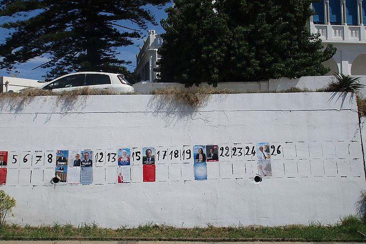 Eine weiße Mauer mit vorgezeichneten Flächen für Wahlplakate. Im Hintergrund Bäume.