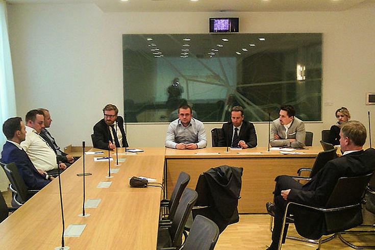 Die rumänischen Besucher sitzen an einem hufeisenförmigen Tisch mit Christian Kattner in einem Seminarraum