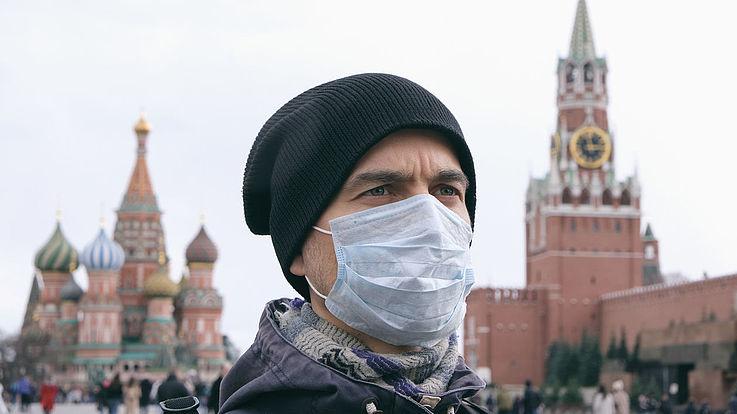 Ein grimmig blickender Mensch mit Mundschutz auf dem roten Platz in Moskau