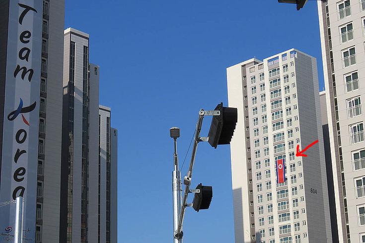 Flagge Nordkoreas die etwa auf halber Höhe aus dem Fenster eines Hochhauses hängt