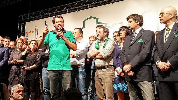Salvini steht auf einer Bühne, umgeben von lauschenden Menschen und spricht offenbar von sich selbst überzeugt in ein Mikro.
