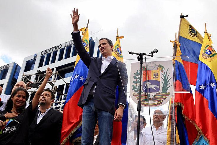 Guaidó, ein junger, schlanker Mann mitte 30 und freundlichem Gesicht winkt auf einem Fahnengeschmückten Podium einer Volksmenge zu.