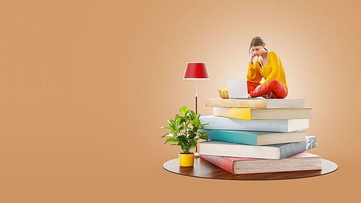 Junge Frau sitzt vor ihrem Laptop auf einem Stapel Bücher. Isoliert.