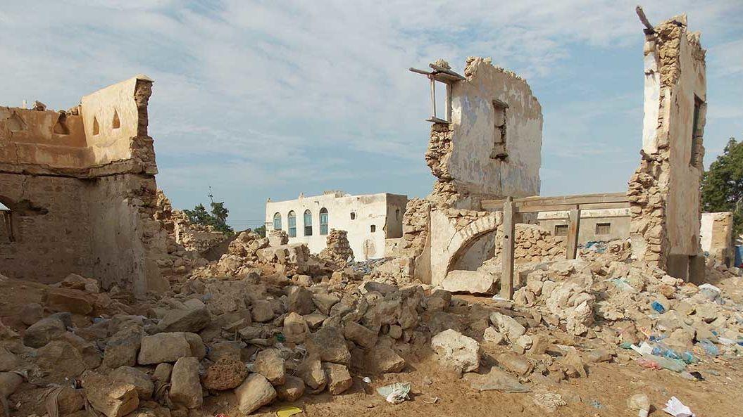 Zerbombte Häuserreste auf sandigem Boden