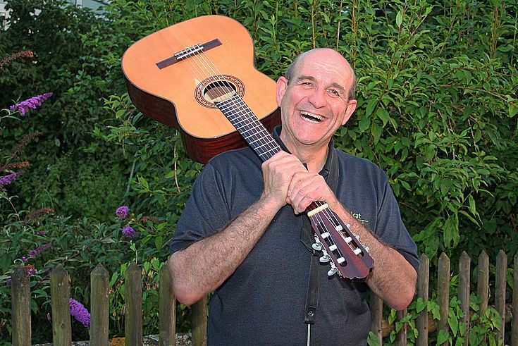 Bradl lacht fröhlich vor einem Gartenzaun. Eine Gitarre hält er falsch herum über die Schulter gelegt, wie eine Schlagwaffe.