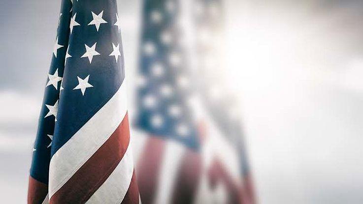 Die US-Flagge vor einem Himmel mit Sonne